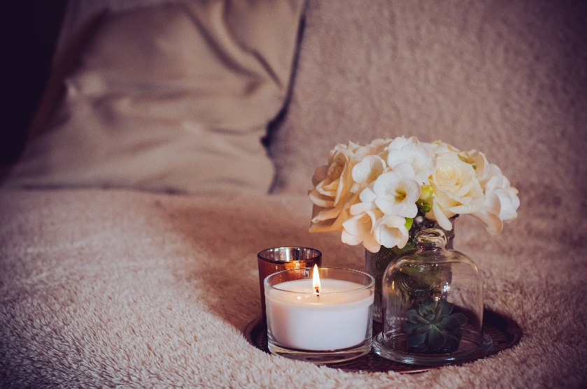 Bouquet of white flowers in a vase, candles on a copper vintage tray, home decor on sofa